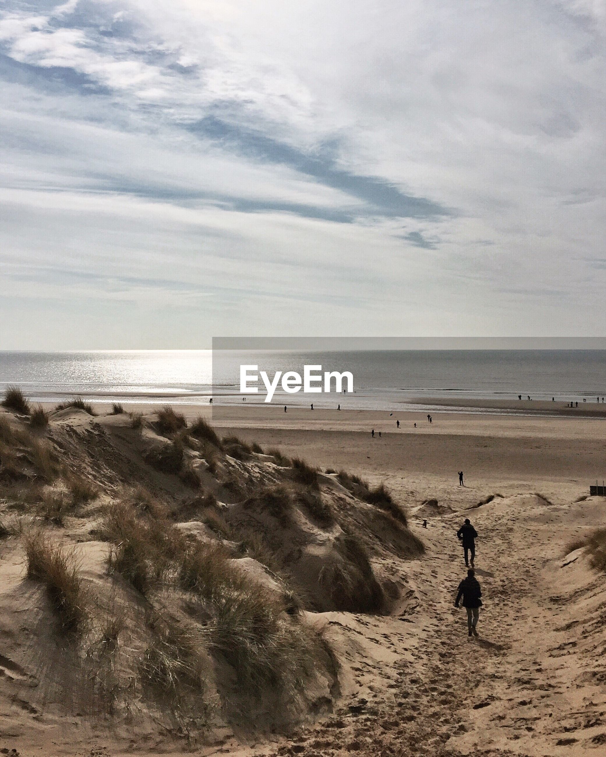 Sand dune at beach against sky