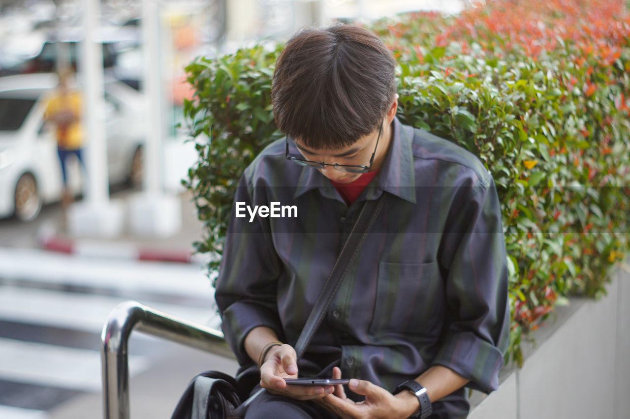 Man talking using mobile phone while sitting outdoors