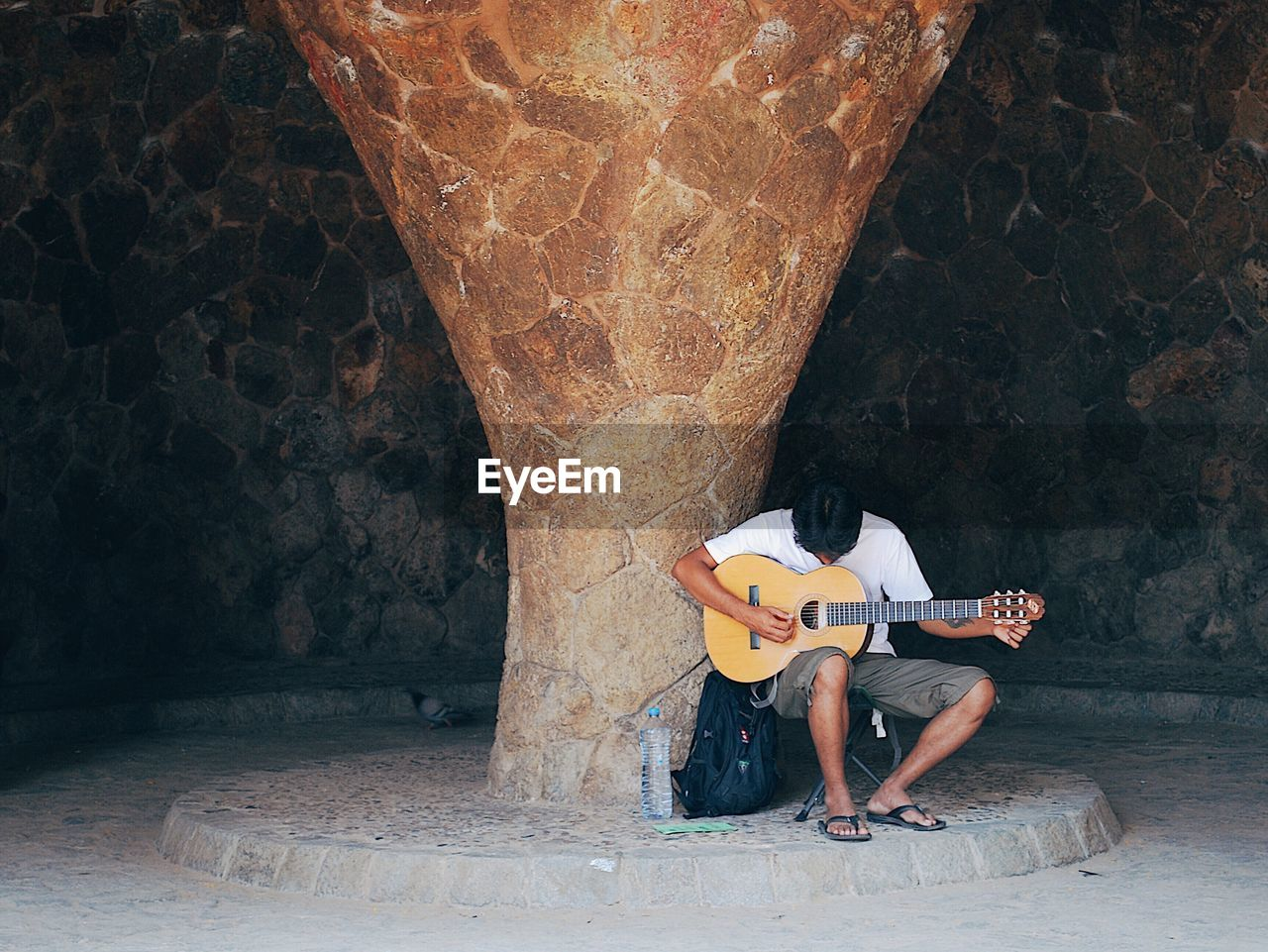 LOW SECTION OF MAN PLAYING GUITAR ON STONE