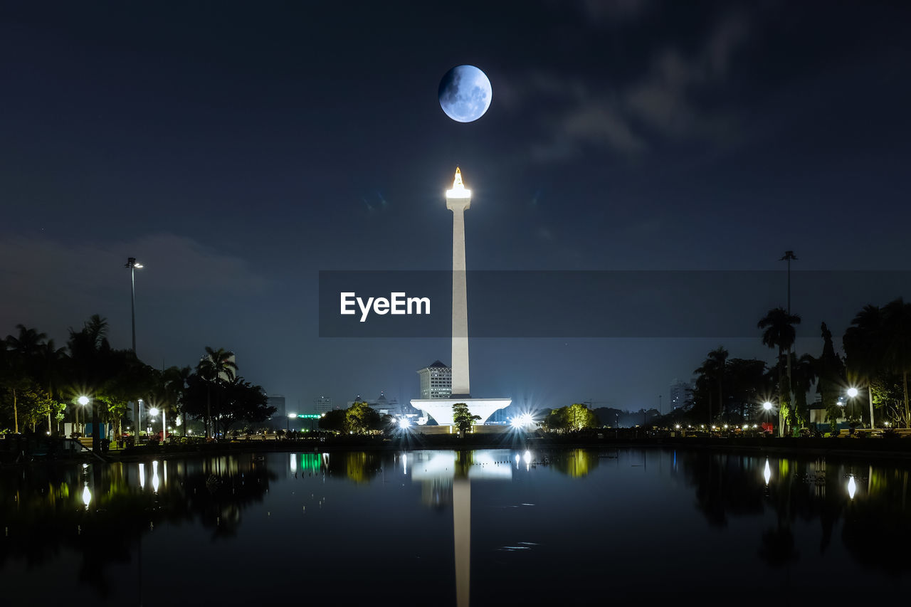 night, sky, illuminated, water, moon, reflection, architecture, nature, built structure, no people, waterfront, lake, tower, full moon, building exterior, tree, outdoors, space, travel destinations, tall - high, moonlight, astronomy