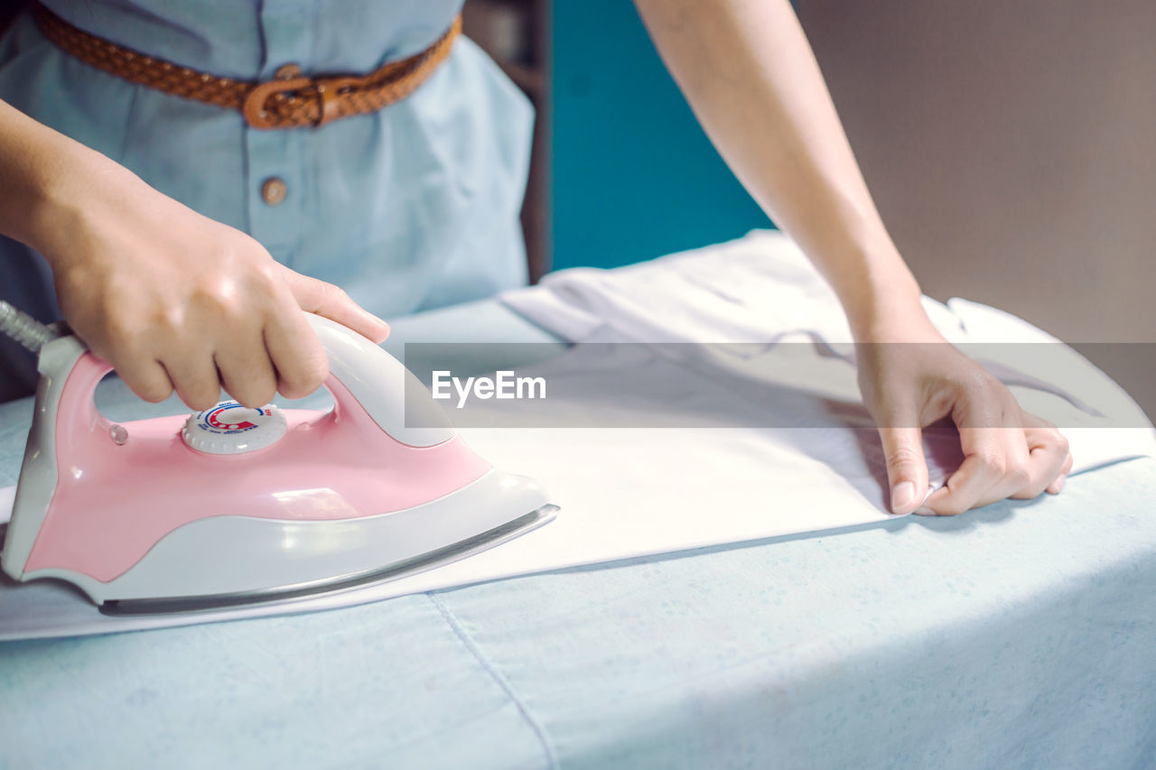 Midsection of woman ironing shirt on board