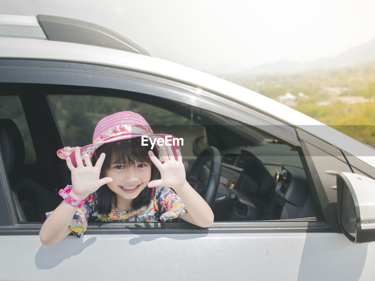 Portrait of smiling girl wearing hat showing hands through car window