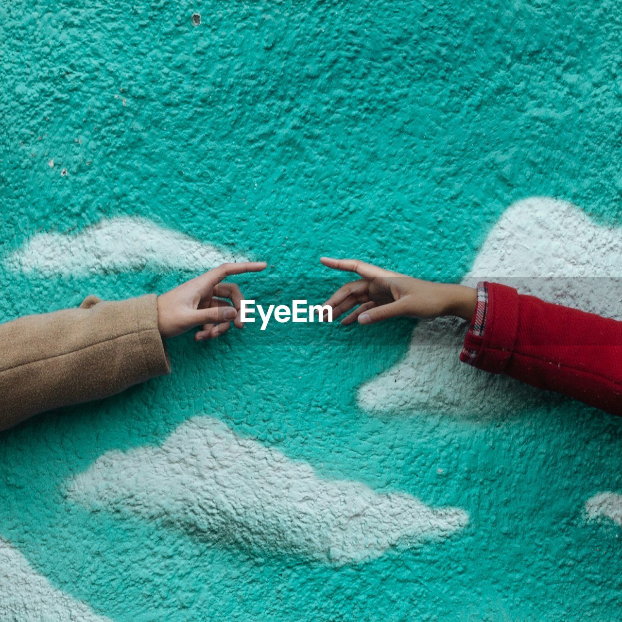 Cropped hand of people against turquoise wall
