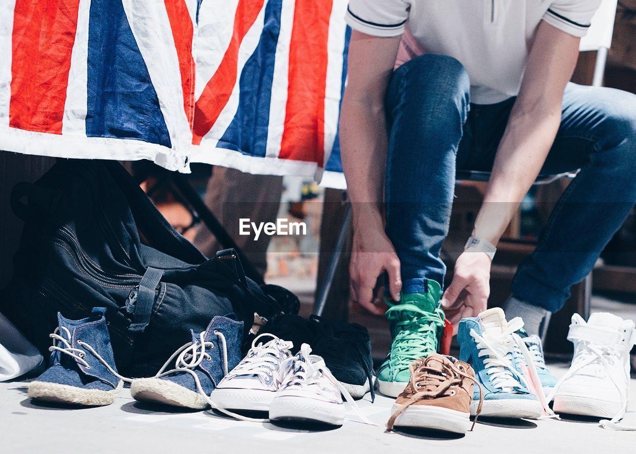Low Section Of Men Wearing Shoe On Floor