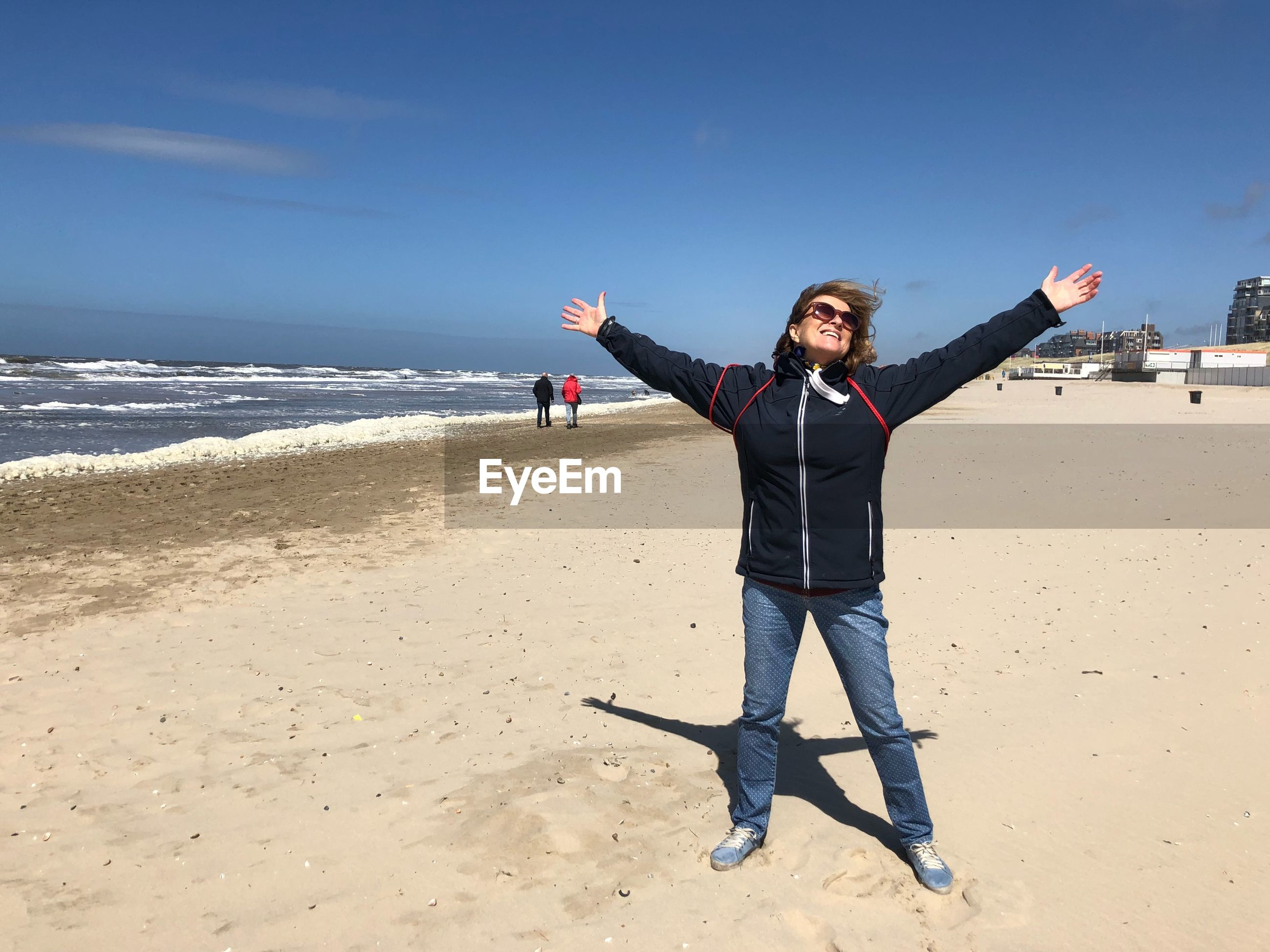 Smiling woman with arms outstretched standing on beach