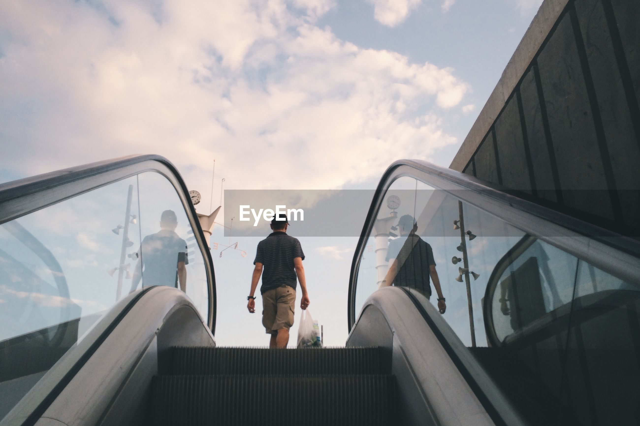 Low angle view of man moving up on escalator