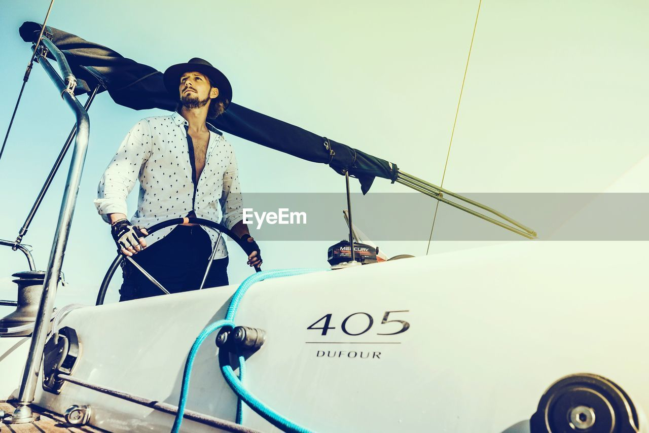 nautical vessel, mode of transport, transportation, real people, boat, leisure activity, one person, outdoors, lifestyles, front view, day, low angle view, sailing, vacations, sky, nature, mast, yacht, young adult, people