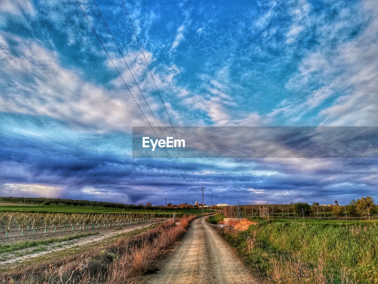 Dirt road passing through landscape against cloudy sky