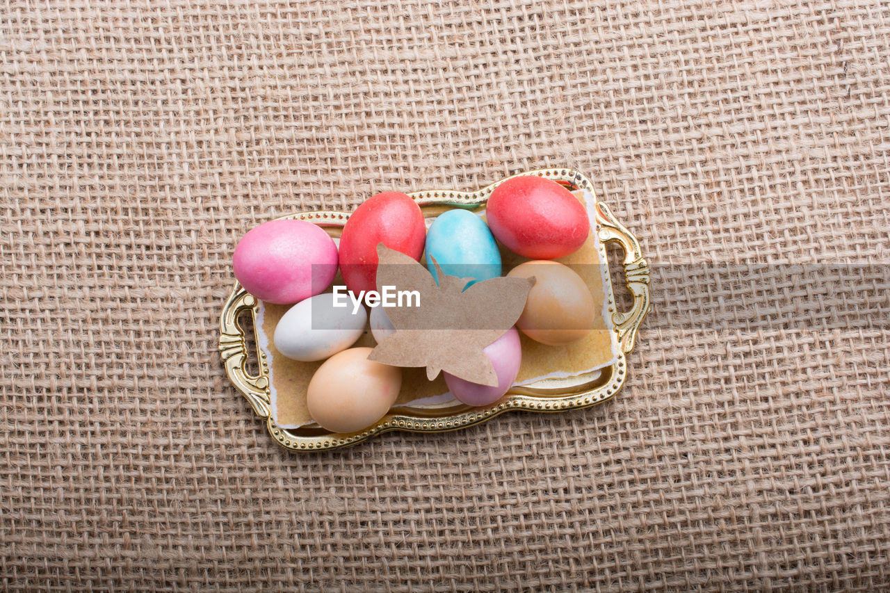 food, egg, food and drink, celebration, easter egg, easter, multi colored, high angle view, holiday, freshness, no people, still life, close-up, basket, indoors, container, sweet, directly above, jute