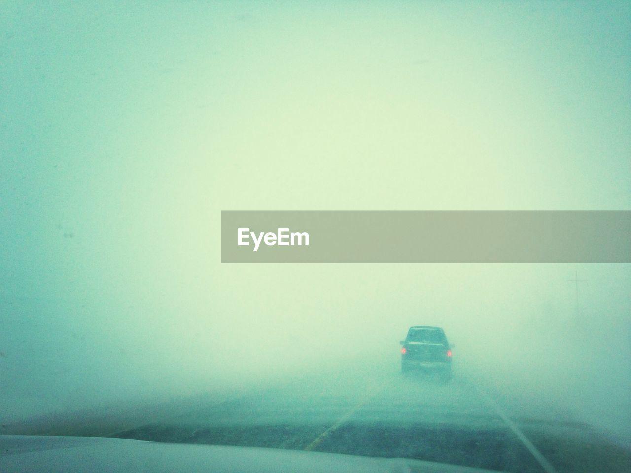 Car on empty misty road