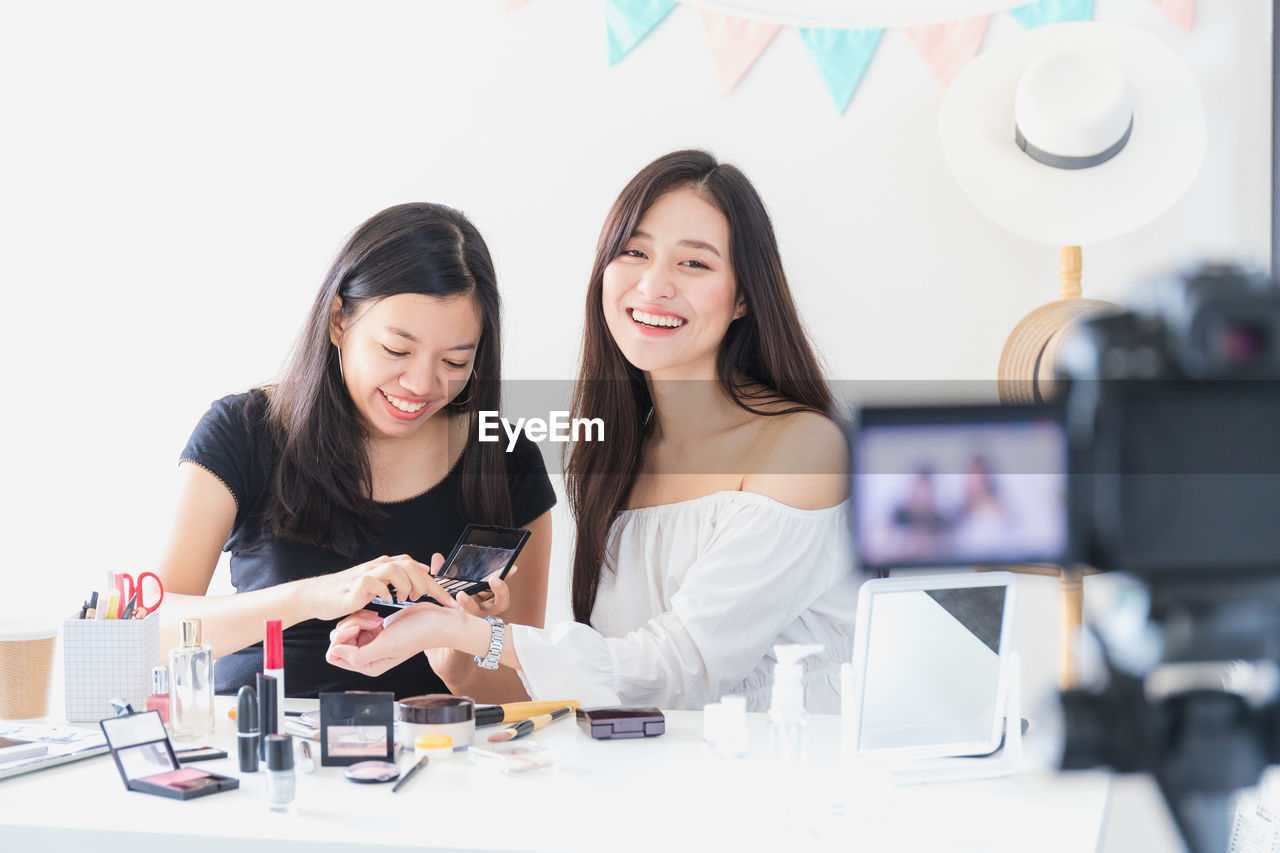 Young women getting photographed while applying make-up