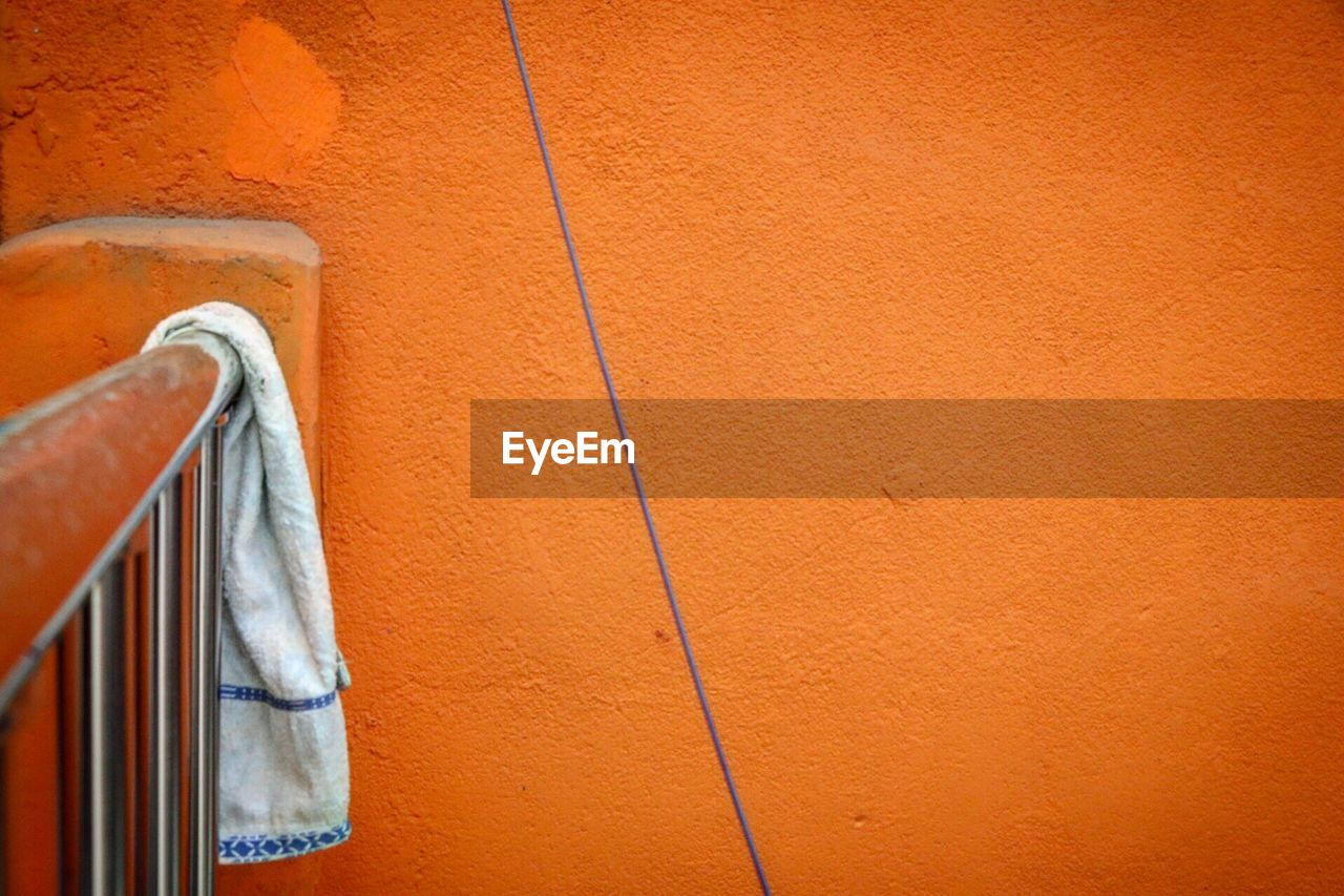 wall - building feature, orange color, architecture, built structure, no people, day, copy space, building exterior, close-up, hanging, wall, metal, outdoors, simplicity, brown, man made object, clothing, casual clothing, textured, drying