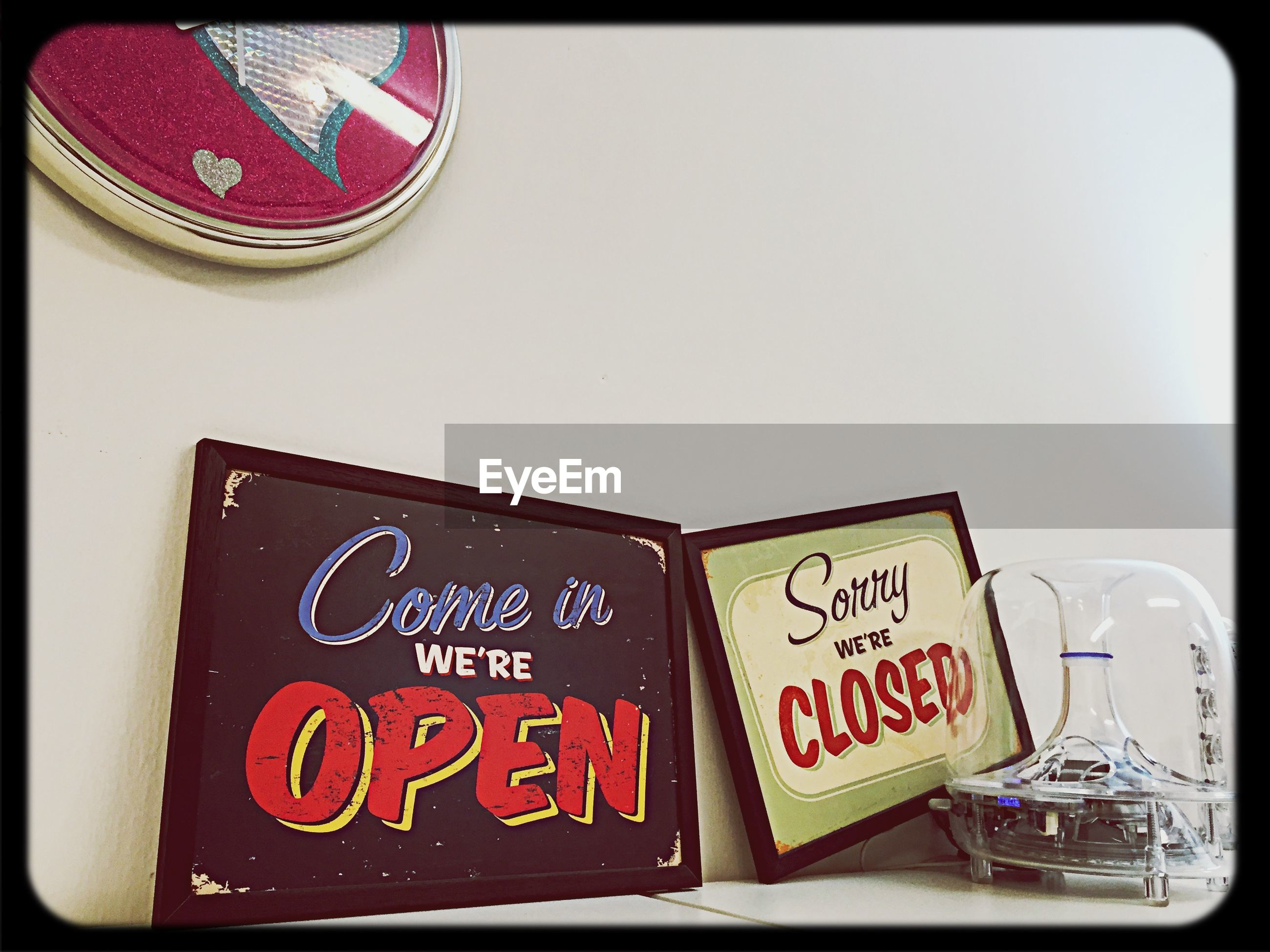 Open and closed signs on table by wall