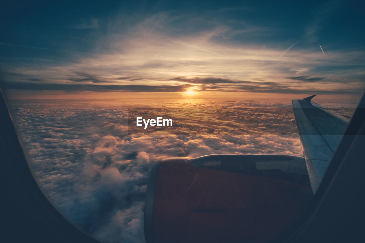 Cropped Image Of Airplane Flying Over Cloudscape Against Sky Seen Through Window