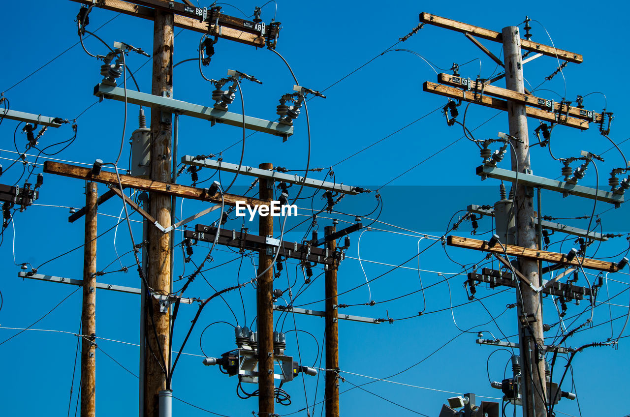 low angle view, blue, technology, sky, cable, electricity, no people, connection, nature, day, power supply, clear sky, power line, fuel and power generation, electricity pylon, outdoors, complexity, sunlight, metal, communication, electrical equipment