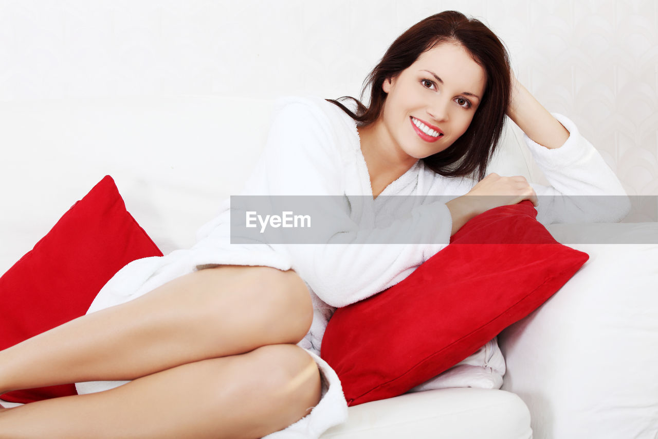 High angle portrait of smiling young woman lying on sofa at home
