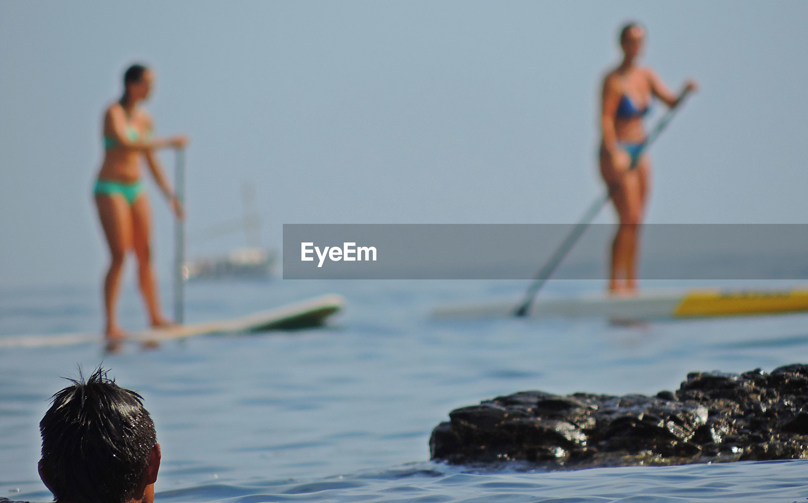 Rear view of man looking at women in biking paddleboarding on sea