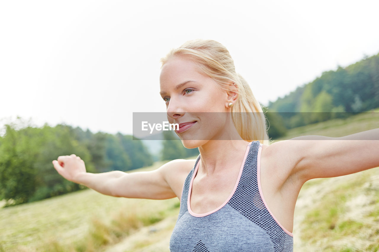 Young Woman With Arms Outstretched Exercising In Park