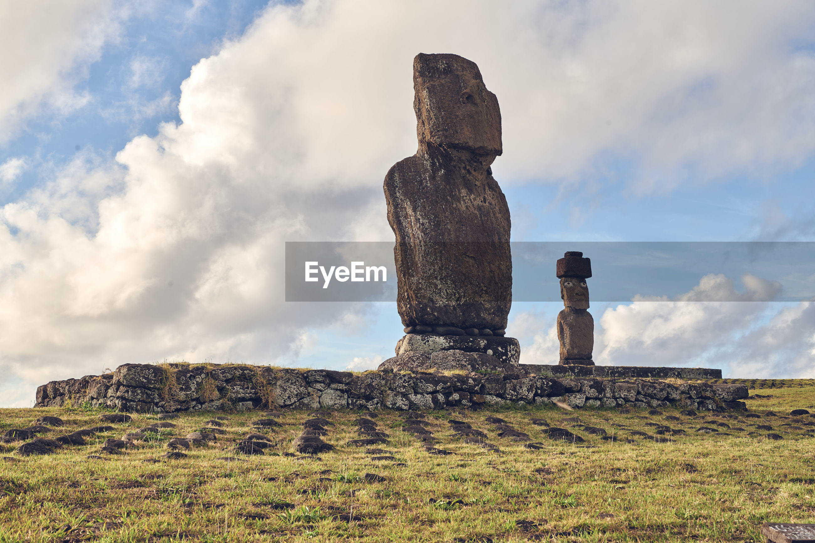 Low angle view of moai statues on field against sky