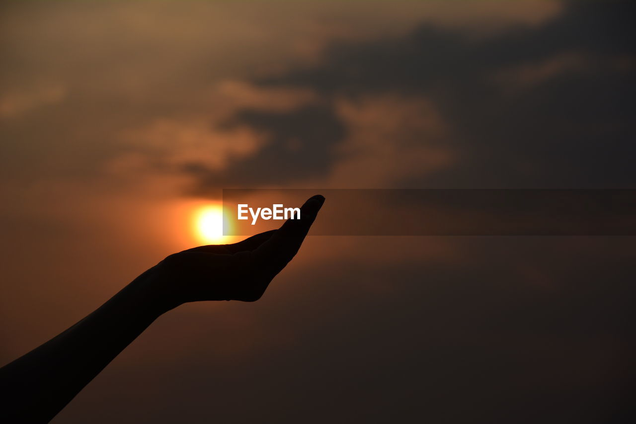 Optical illusion of silhouette hand holding sun sky during sunset