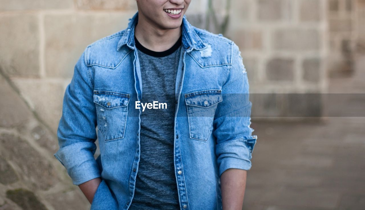 real people, casual clothing, jeans, one person, leisure activity, outdoors, lifestyles, day, front view, standing, denim jacket, focus on foreground, smiling, architecture, young adult, close-up