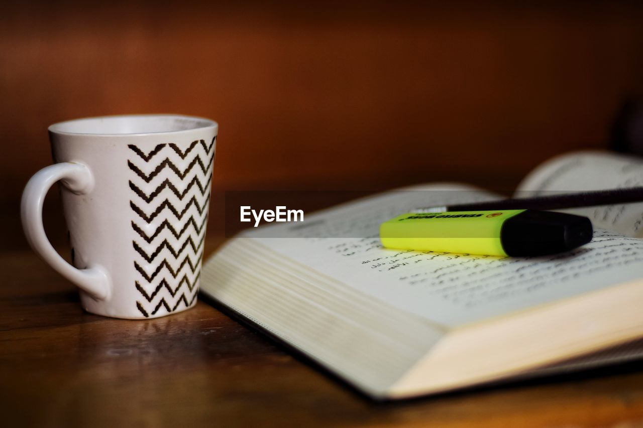 table, cup, mug, still life, coffee cup, indoors, food and drink, drink, communication, selective focus, coffee, coffee - drink, book, refreshment, no people, wood - material, publication, close-up, paper, pen, note pad, crockery, tea cup