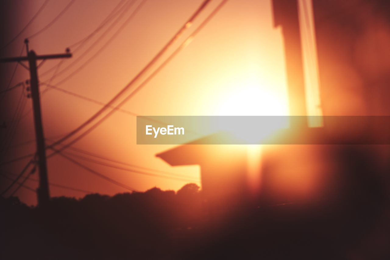 Low angle view of silhouette electricity pylon at sunset
