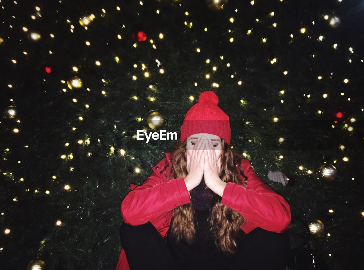 Woman Covering Face With Hands Against Christmas Tree At Night