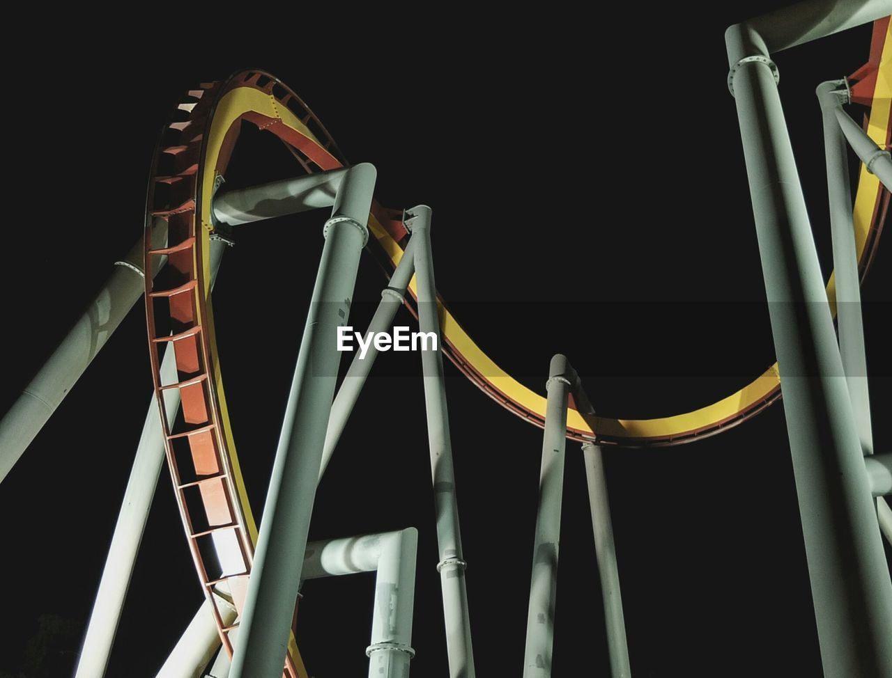 Low Angle View Of Rollercoaster Tracks At Night