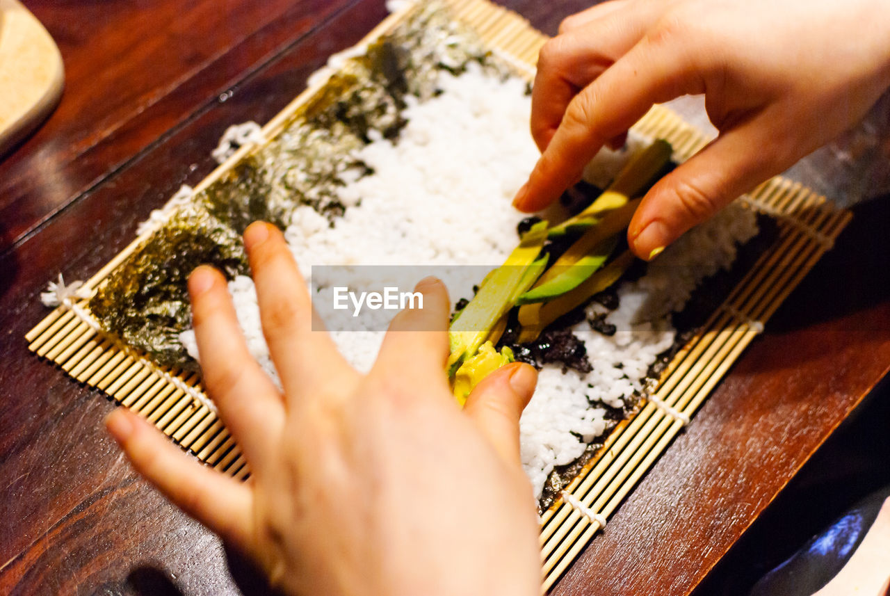 human hand, hand, human body part, food, one person, food and drink, wood - material, selective focus, preparation, holding, indoors, real people, close-up, unrecognizable person, preparing food, adult, women, freshness, finger, table knife, japanese food