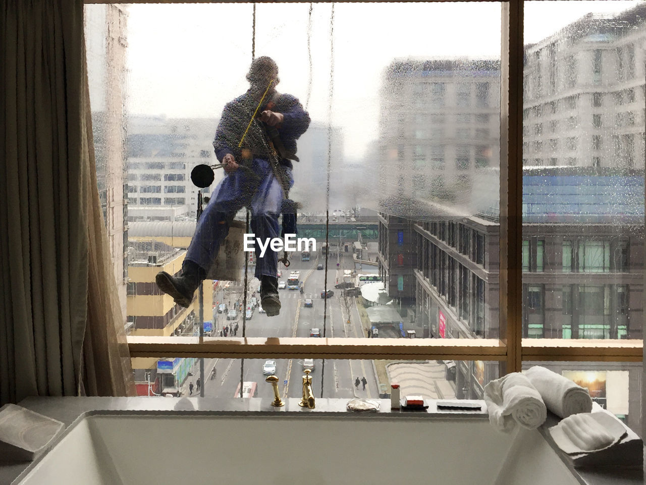 Man hanging while cleaning window