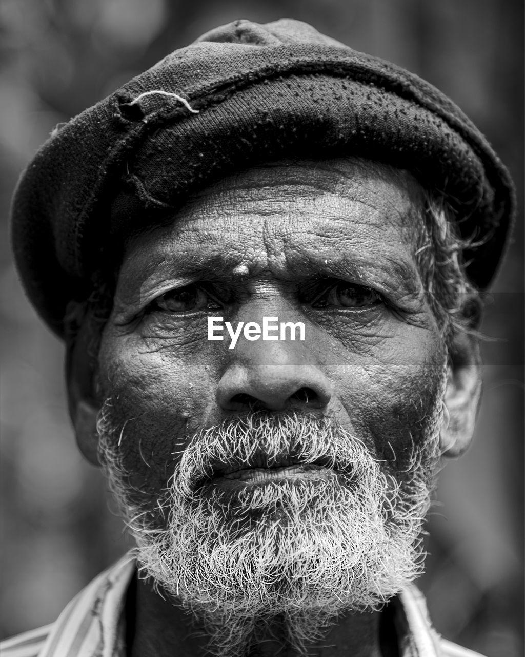 Close-up portrait of mature man wearing hat
