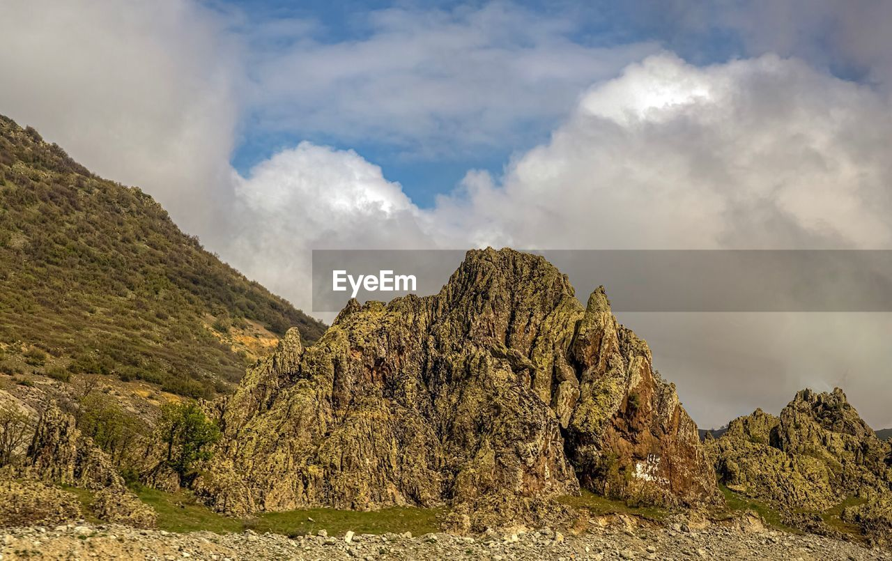 cloud - sky, sky, beauty in nature, scenics - nature, tranquility, tranquil scene, mountain, non-urban scene, nature, rock, day, rock formation, no people, rock - object, solid, idyllic, environment, physical geography, plant, outdoors, formation, eroded, mountain peak