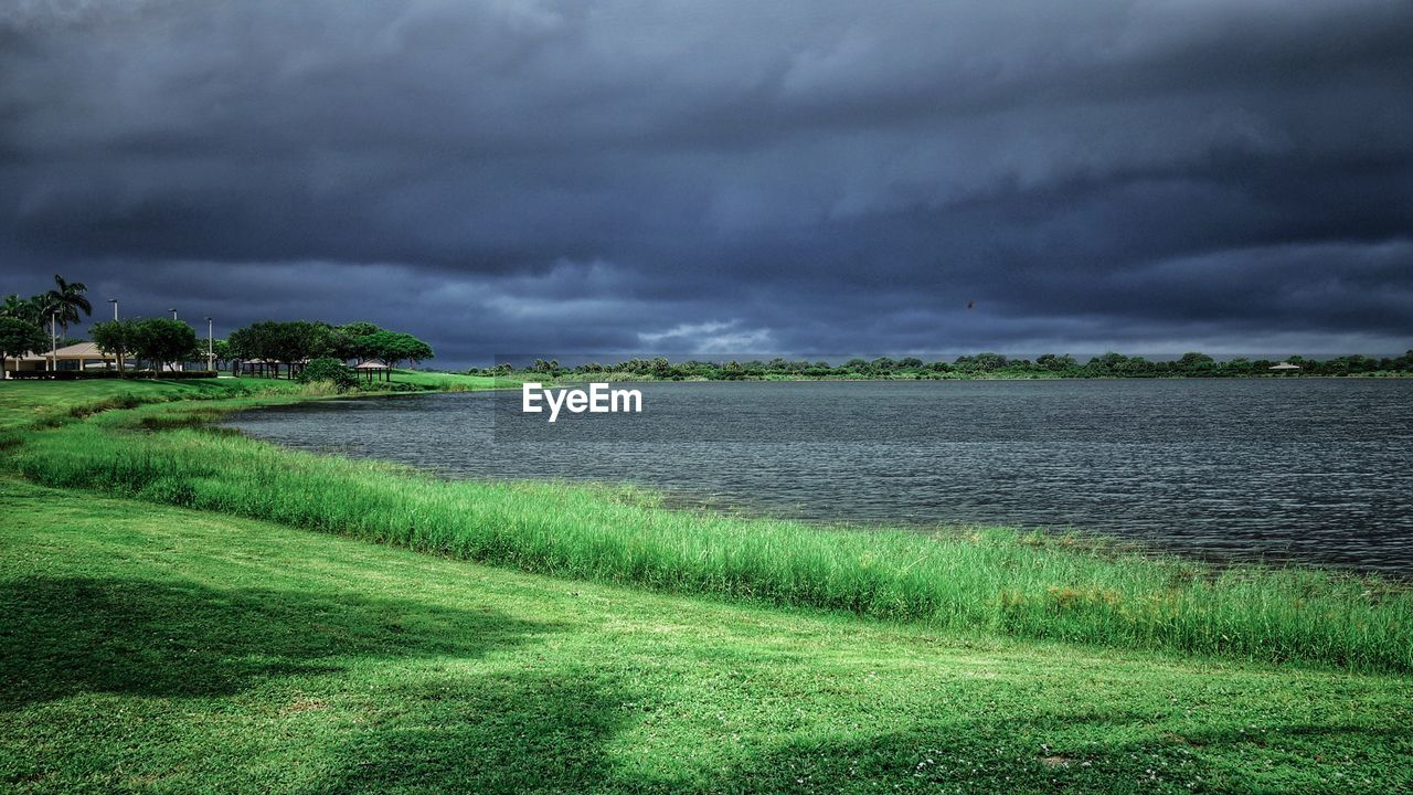 cloud - sky, grass, nature, storm cloud, field, beauty in nature, sky, landscape, tranquility, green color, tranquil scene, scenics, no people, weather, outdoors, day, growth, tree, water