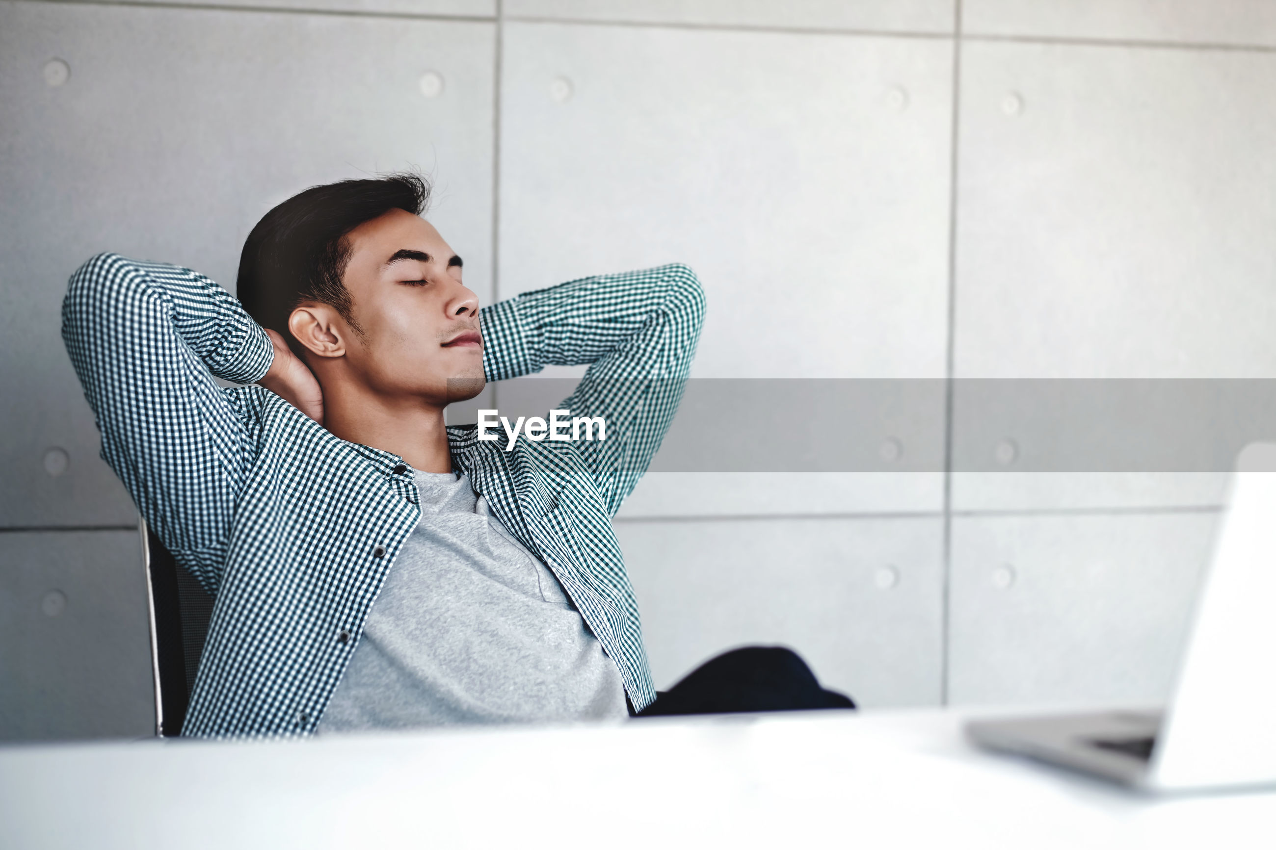 Man relaxing with hands behind head while sitting on chair against wall