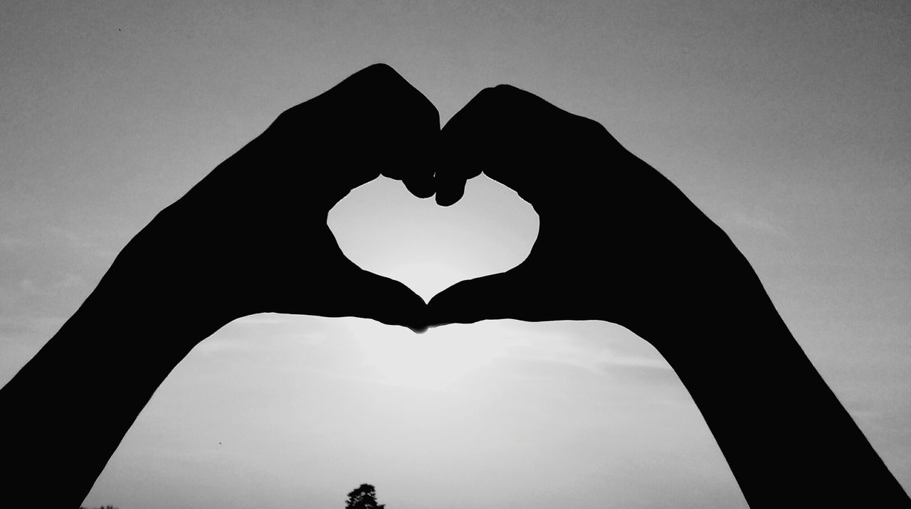 heart shape, forming, human hand, love, shape, silhouette, sky, real people, clear sky, low angle view, close-up, one person, outdoors, human body part, day