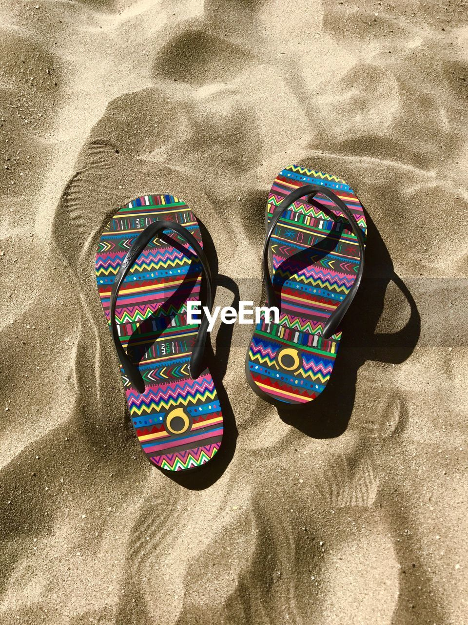HIGH ANGLE VIEW OF SHOES ON SANDY BEACH