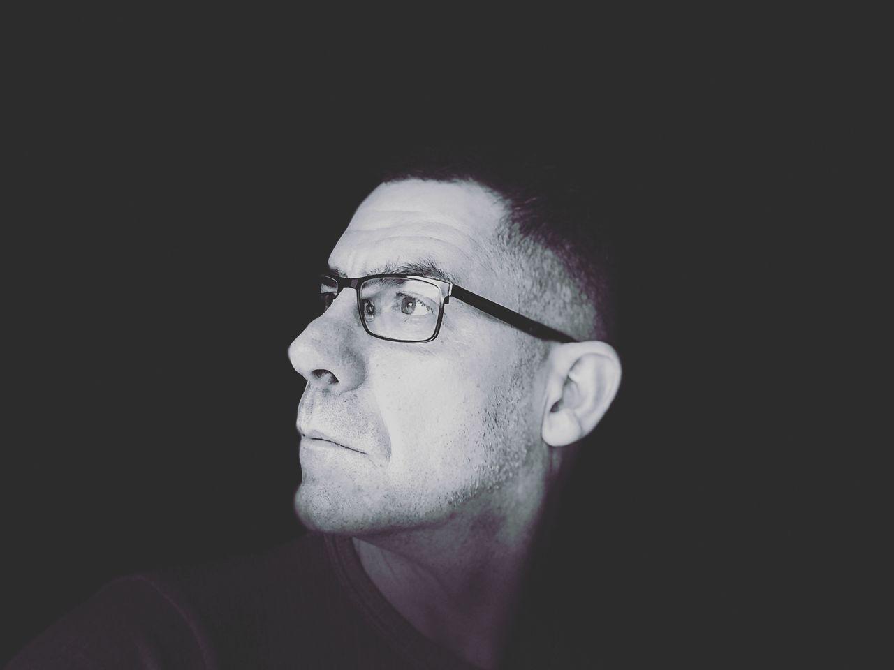 Close-Up Of Thoughtful Mature Man Wearing Eyeglasses Against Black Background