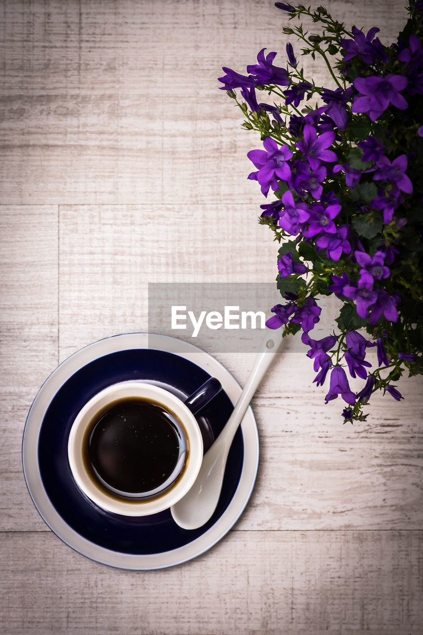 table, flowering plant, freshness, cup, refreshment, drink, food and drink, flower, mug, directly above, coffee - drink, coffee cup, indoors, coffee, high angle view, plant, no people, wood - material, still life, vase, purple, crockery, flower arrangement, bouquet