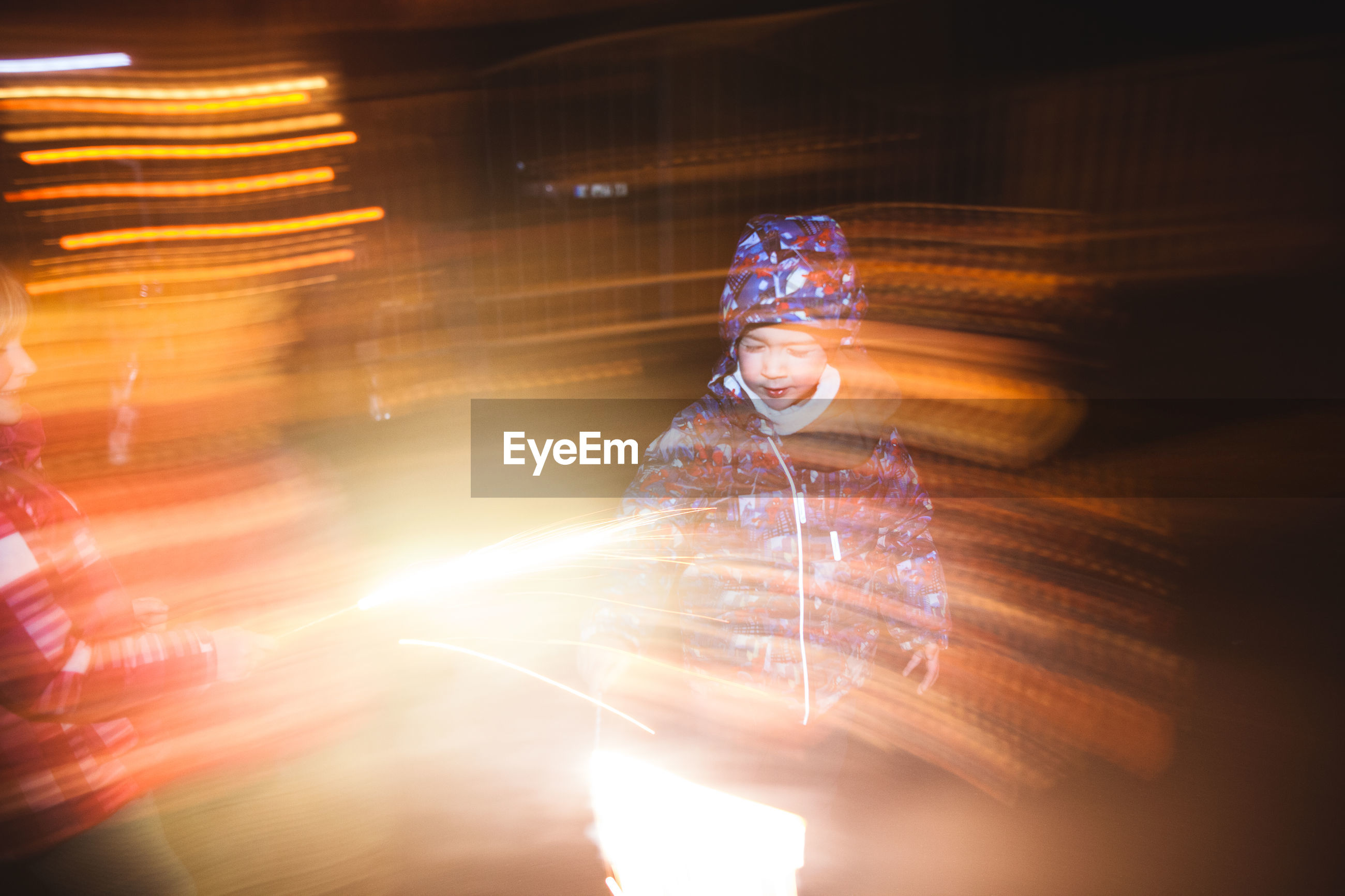 Boy standing by light painting at night