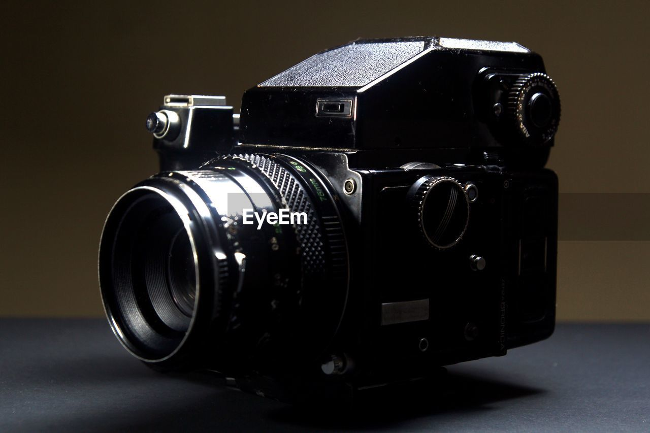 camera - photographic equipment, retro styled, photography themes, technology, indoors, still life, close-up, single object, studio shot, no people, photographic equipment, antique, black color, table, lens - optical instrument, camera, metal, vintage, analog, digital camera, silver colored, chrome