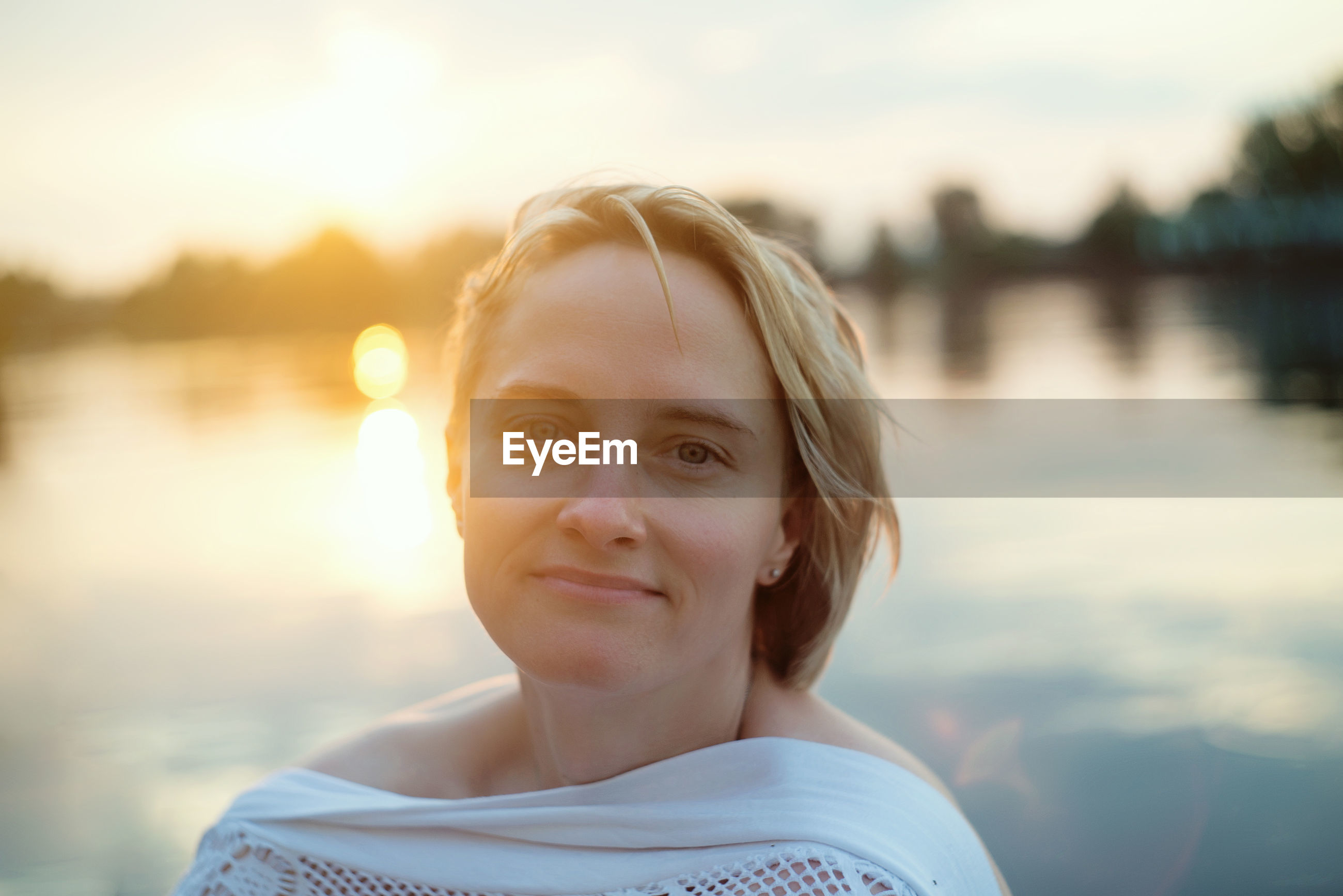 portrait, one person, water, headshot, female, portrait photography, blond hair, nature, smiling, lake, looking at camera, sunlight, women, sky, sunset, person, emotion, happiness, adult, focus on foreground, lens flare, hairstyle, child, back lit, blue, casual clothing, leisure activity, lifestyles, outdoors, front view, reflection, day, human face, childhood, young adult, relaxation, summer, skin, trip, vacation, standing, copy space