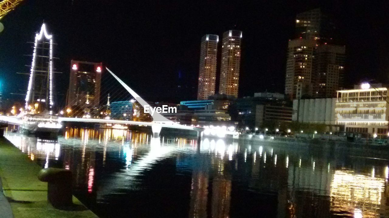 illuminated, water, architecture, night, building exterior, built structure, waterfront, reflection, city, travel destinations, river, skyscraper, no people, outdoors, modern, sky, cityscape