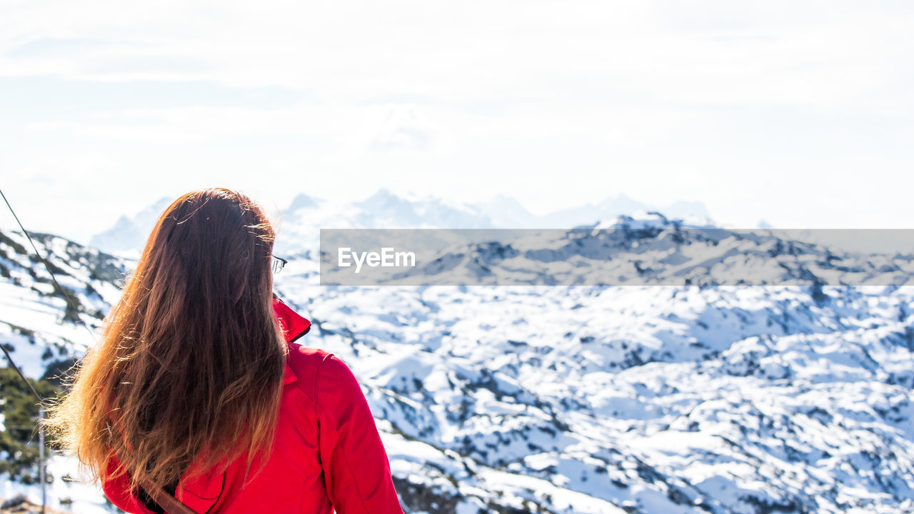 Rear view of woman in front of snow covered mountain