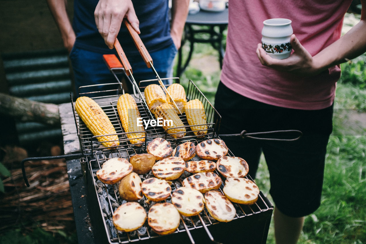 food and drink, food, real people, midsection, freshness, barbecue grill, day, preparation, barbecue, standing, holding, men, lifestyles, outdoors, people, hand, human hand, corn, preparing food