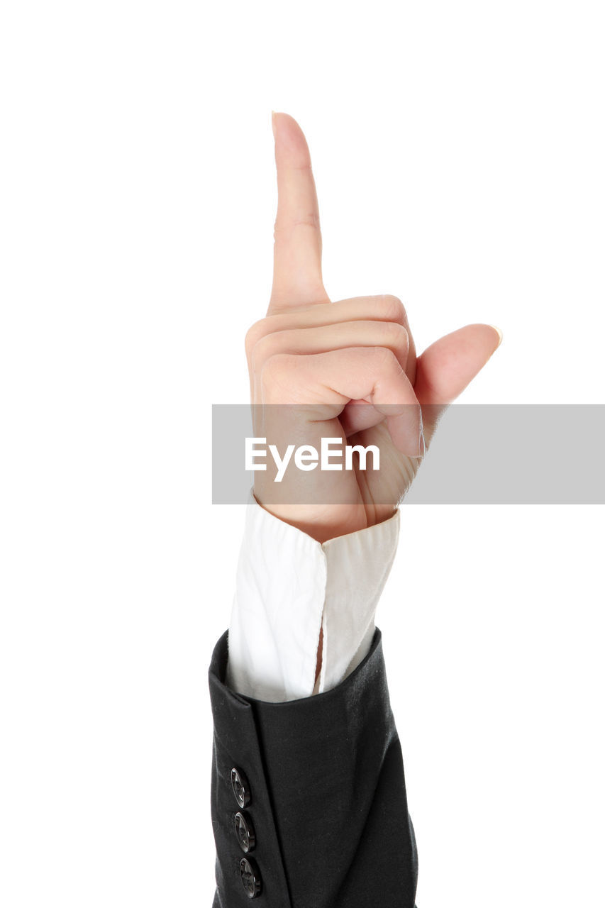 Cropped hand of business person pointing against white background