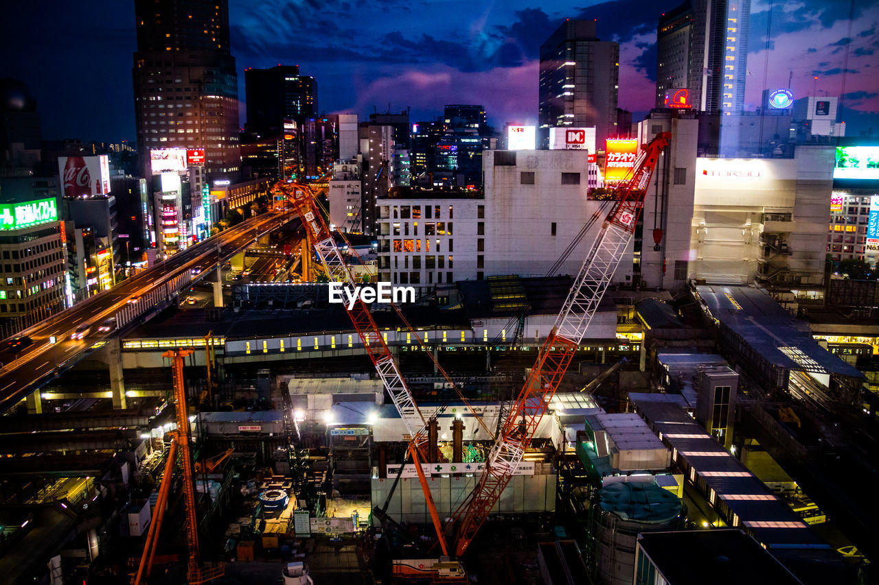 High Angle View Of Cranes At Construction Site In City At Night