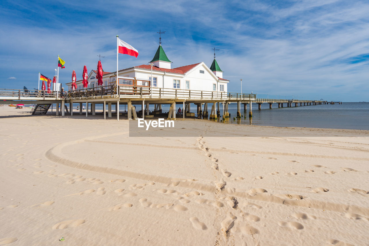 beach, sand, sea, water, built structure, sky, nature, architecture, flag, outdoors, day, vacations, tranquility, no people, horizon over water, scenics, beauty in nature