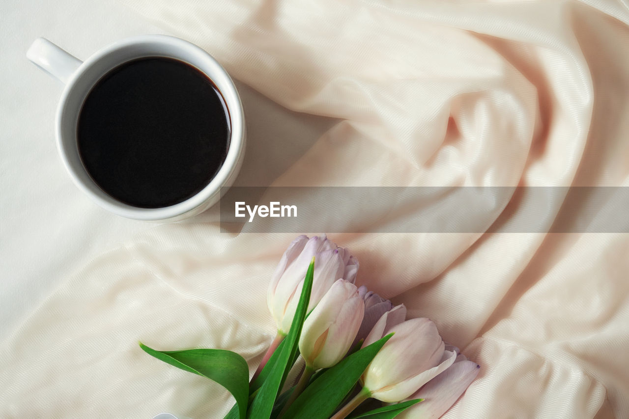 HIGH ANGLE VIEW OF BLACK COFFEE AND WHITE ROSE ON TABLE