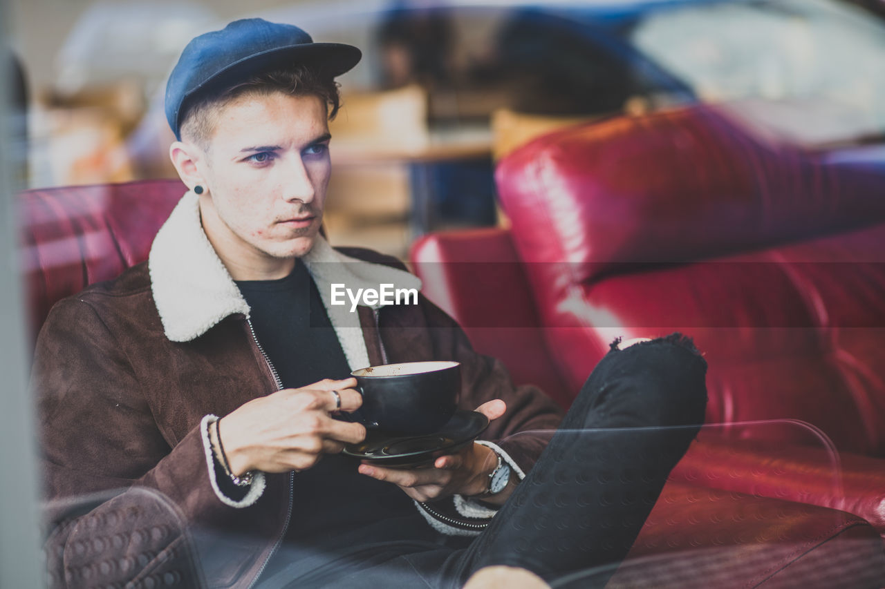 Handsome Man Sitting With Coffee At Cafe Seen From Window